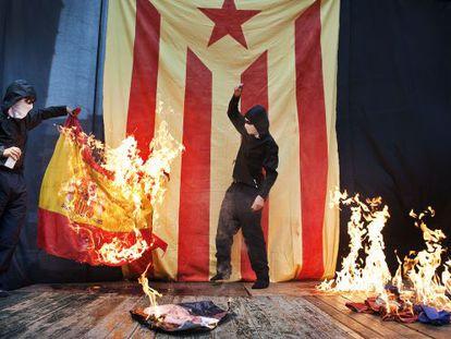 Un encapuchado quema un retrato del Rey y una bandera española, en octubre de 2019 en Barcelona.
