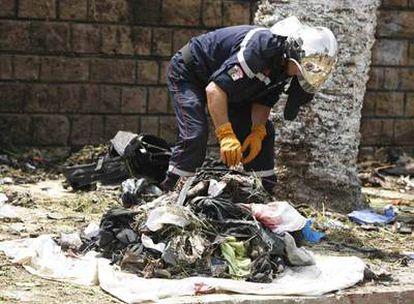 Un efectivo de los servicios de emergencias inspecciona el lugar donde esta mañana se ha registrado un atentado suicida cerca de Argel.