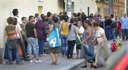 Decenas de personas hacen cola en la puerta de un centro de ayuda social en Valencia.