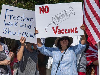 Un grupo de californianos se manifiestan contra las medidas de confinamiento con una pancarta contra las vacunas.