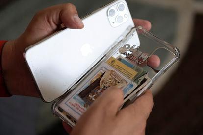 Guillermo Valencia, muestra sus escapularios que resguarda en su celular.