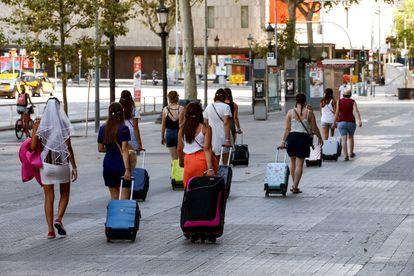 Varias turistas caminan por la Plaza Cataluña de Barcelona.