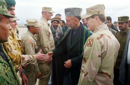 Hamid Karzai (centro), presidente de Afganistán, saluda a un grupo de soldados junto al comandante de las tropas terrestres estadounidenses en Afganistán, el general Franklin Lee Hagenbeck, en la base de Bagram en Afganistán en 2002.