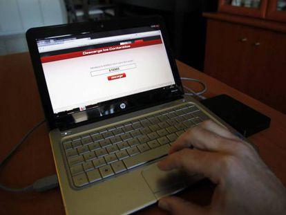 Una persona descarga contenidos piratas 'online' desde un ordenador portátil.
