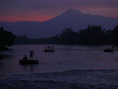 Varias balsas transportan pasajeros y mercancías a través del río Suchiate entre México y Guatemala.