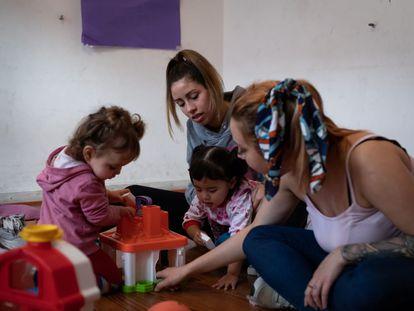 Varias madres adolescentes juegan con sus hijas.