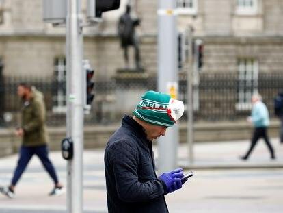 Un hombre consulta su teléfono, este martes en las calles de Dublín.
