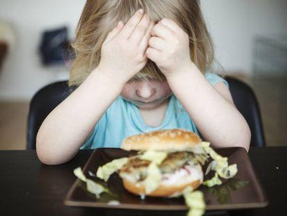 Una niña no quiere comer una hamburguesa.