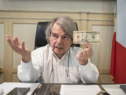 El Renato Brunetta, ministro Italiano de Administraciones Públicas, muestra un billete de 10 dólares con el rostro de Alexander Hamilton durante la entrevista con EL PAÍS.