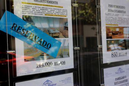Anuncios de pisos y casas en venta y alquiler en el escaparate de una inmobiliaria en Madrid.