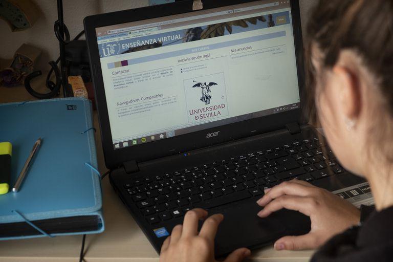 Una estudiante accede a las clases 'online' de la Universidad de Sevilla con un ordenador portátil.