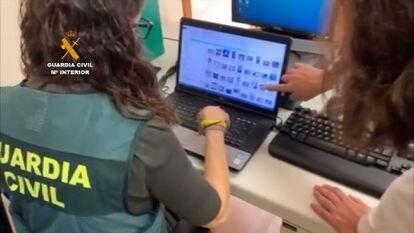 Agentes de la Guardia Civil revisan el equipo informático del detenido.