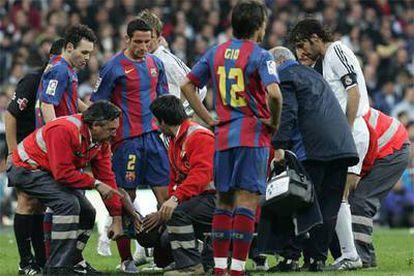 Los jugadores de los dos equipos observan a Eto'o en la camilla en la que abandonó lesionado el terreno de juego.