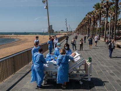Personal sanitario del hospital del Mar de Barcelona, lleva a un paciente de covid-19 a la playa como parte de un programa para humanizar las UCI.