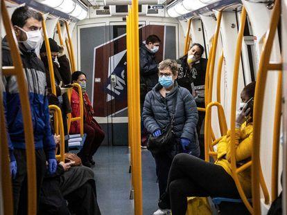 Usuarios protegidos con mascarillas en el interior de un vagón del metro de Madrid, en abril.