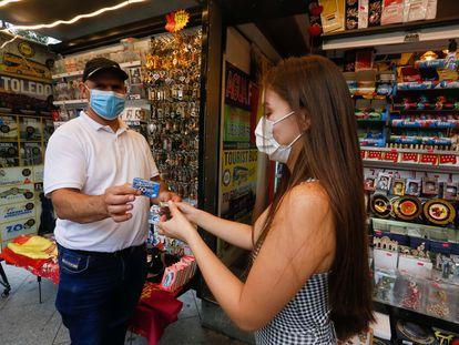 Una joven compra chicles en un quiosco del centro de Madrid.