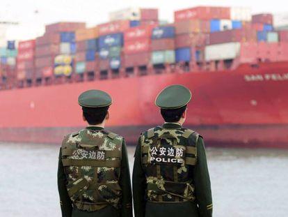 Dos policías esperan la llegada de un buque de carga en el puerto de Qingdao, China.