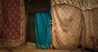 Una niña se esconde detrás de unas telas que hacen de muro de una casa improvisada en Adiel Khan, en las afueras de Peshawar.
