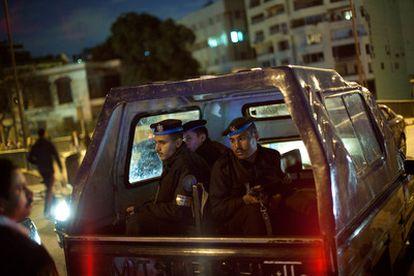 Un vehículo que traslada a policías egipcios es detenido en un puesto de control establecido por vecinos de un barrio de El Cairo, en uno de los extremos de un puente sobre El Nilo.
