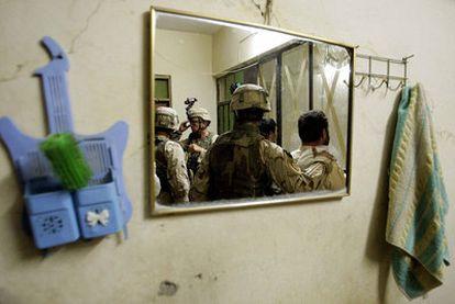 Soldados de la brigada Stryker del Ejército estadounidense, reflejados en el espejo de una vivienda que inspeccionan a la búsqueda de insurgentes en Mosul, en julio de 2005.