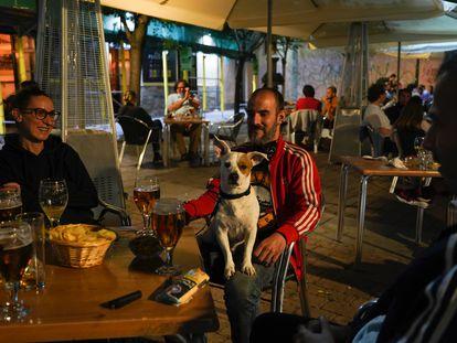 Carolina y Asier junto al pero Lupo y unos amigos en la terraza del restaurante Conache, en la plaza de San Ildefonso de Malasaña