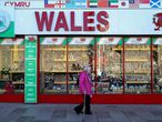 """(FILES) In this file photo taken on September 27, 2020 a woman wearing a protective face visor walks past a souvenir shop selling Welsh-themed items, in Cardiff, south Wales. - Wales will impose a full """"firebreak"""" lockdown for two weeks from October 23, to try to reduce a soaring number of new coronavirus cases, First Minister Mark Drakeford said on October 19, 2020. Under the new rules, everyone will be required to stay at home with only critical workers expected to go to their workplaces. (Photo by Geoff Caddick / AFP)"""