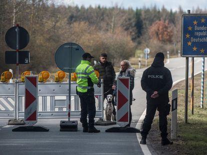 Un policía habla con una pareja ayer en la frontera entre Alemania y la República Checa.