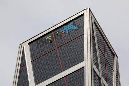 Varios operarios quitan el logotipo de Bankia para incorporar, sobre las ventanas más altas del edificio de Torre Europa de Madrid, la imagen de CaixaBank.