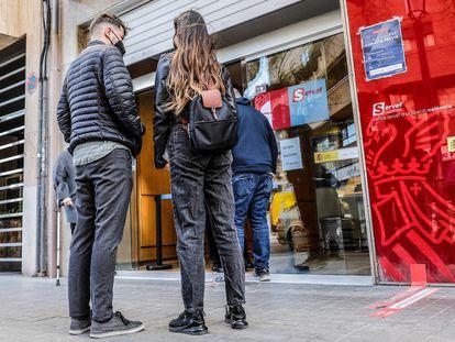 Varias personas en Valencia en la puerta de una oficina pública de empleo.