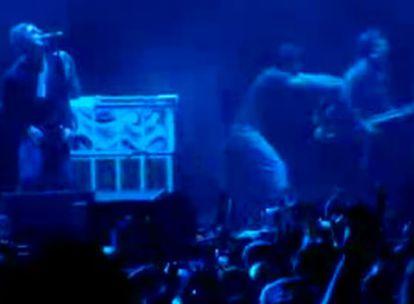 Momento en el que Noel Gallagher, a la derecha con una guitarra, es empujado por un espectador