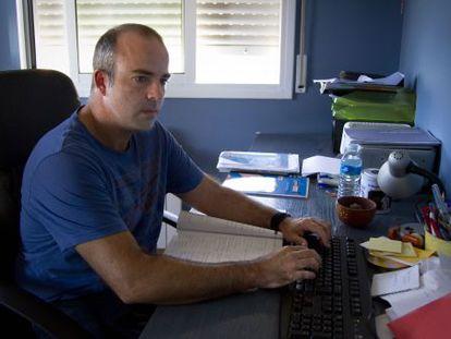 Julio Salom, ante el ordenador, en su casa.