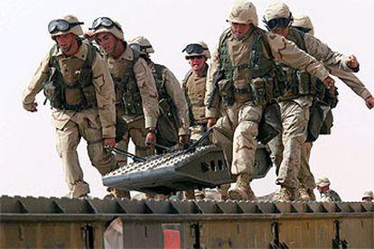 <i>Marines</i> del 8º Batallón de Apoyo de Ingerniería trasladan una pieza de construcción en un campamento al norte de Kuwait.