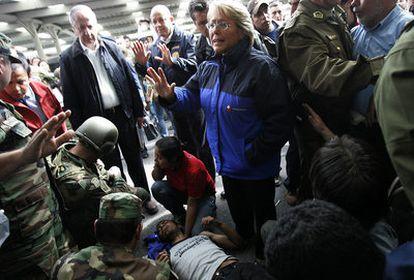 La presidenta de Chile, Michelle Bachelet, al lado de un superviviente del seísmo que sufrió un ataque epiléptico hoy en Concepción