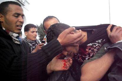 Un grupo de personas auxilia a un joven herido en las protestas de Túnez.