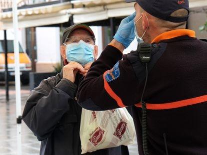 Un policía local explica a un ciudadano cómo colocarse la mascarilla como protección frente a la covid-19 en Palma de Mallorca.