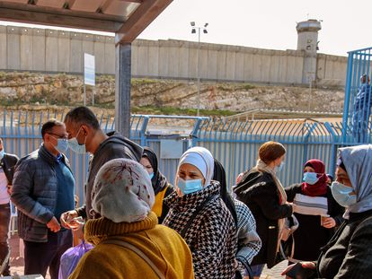 Varios palestinos esperan a ser vacunados por sanitarios israelíes, el martes en el paso de Qalandia, entre Cisjordania e Israel.