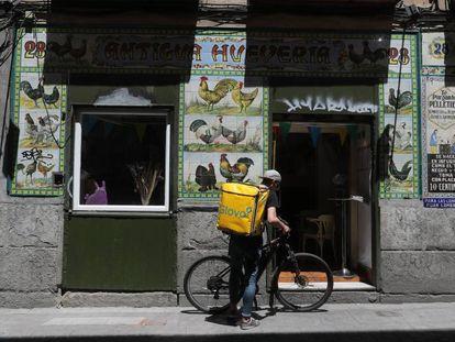 Un repartidor de comida, ante la antigua fachada de un local reconvertido en restaurante en Madrid.