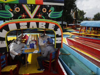 """Médicos examinan a un hombre para detectar COVID-19 a bordo de una """"trajinera"""" en  la alcaldía Xochimilco en la Ciudad de México, México."""