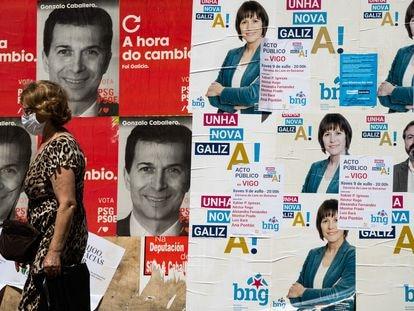 Una mujer pasa ante los carteles electorales de los candidatos del PSdeG, Gonzalo Caballero, y del BNG, Ana Ponton  a la presidencia de la Xunta de Galicia.