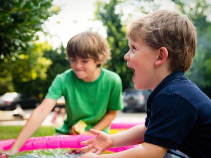 Dos niños juegan en el jardín.