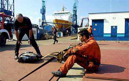 Bomberos y trabajadores, después de las labores de extinción del incendio en un barco en los astilleros de Vigo.