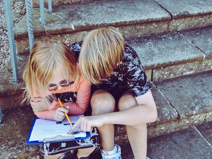 Dos niños repasan la tarea, sentados en una escalera.
