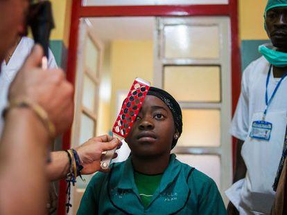 Un médico hace una prueba de visión a una joven paciente en el hospital de Foumban, en el oeste de Camerún.
