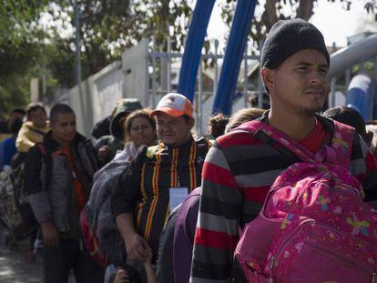 Integrantes de la caravana migrante esperan en fila para entrar al albergue temporal en Tijuana.