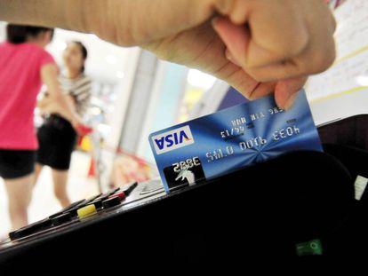 Un hombre utiliza una tarjeta de crédito de Visa.