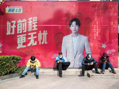 Cuatro repartidores con mascarillas junto a una boca de metro en Shangai, el 27 de febrero pasado.
