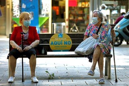 Dos mujeres conversan en un banco de L'Hospitalet (Barcelona), el jueves pasado.