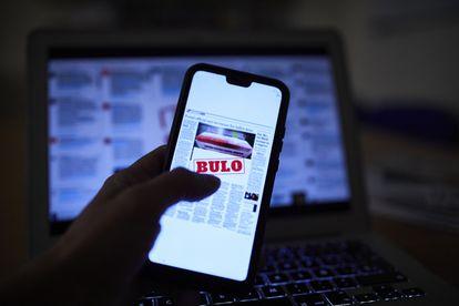 Una persona lee una noticia falsa en su móvil.