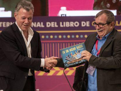 Juan Manuel Santos le regala el libro 'En un mismo barco' a Rodrigo Londoño en la FIL de Guadalajara del 2019.