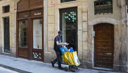Un cartero pasa por delante de un bajo comercial en una calle de Barcelona